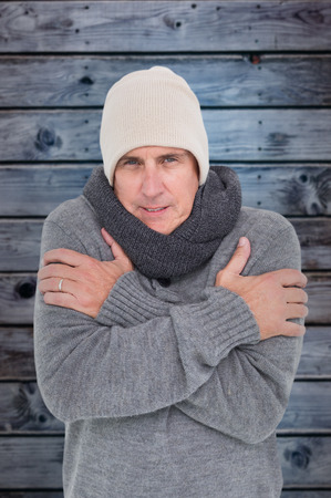 shivering: Casual man shivering in warm clothing against wooden background in blue