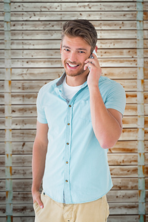 pale wood: Handsome young man talking on his smartphone against wooden background in pale wood