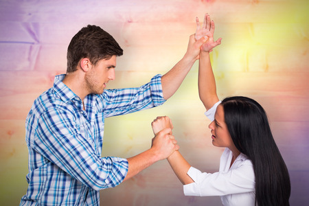 overpowering: Aggressive man overpowering his girlfriend against yellow and purple planks