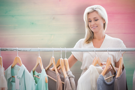 clothes rail: Pretty blonde looking through clothes rail against pink and green planks Stock Photo