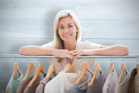 clothes rail: Pretty blonde smiling at camera by clothes rail against bleached wooden planks background