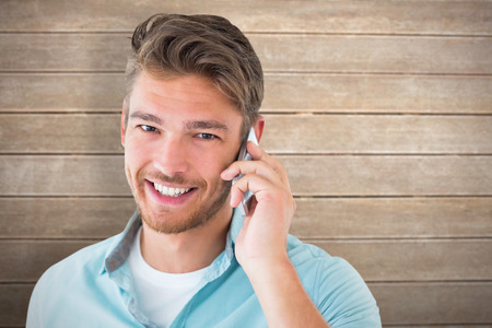 chinos: Handsome young man talking on his smartphone against wooden surface with planks Stock Photo
