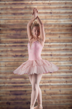 Pretty ballerina in pink against wooden planks photo