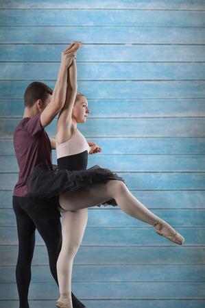 Ballet partners dancing against wooden planks photo