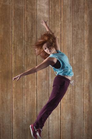 computer dancing: Pretty break dancer against wooden planks background