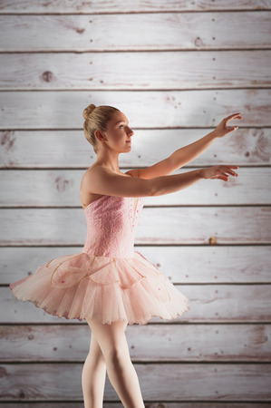 computer dancing: Pretty ballerina in pink  against wooden planks