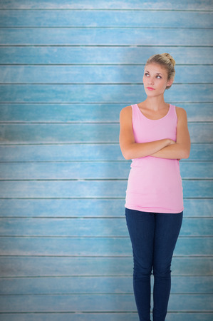 apprehensive: Pretty young blonde in pink thinking with arms crossed against wooden planks