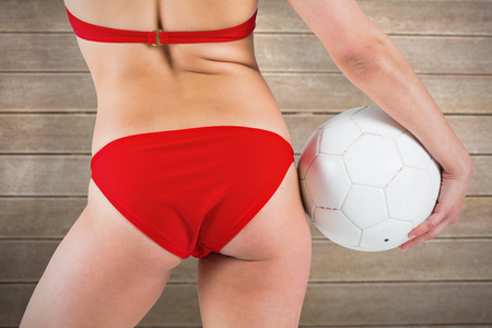 sexy lady: Fit girl in bikini holding football against wooden surface with planks Stock Photo
