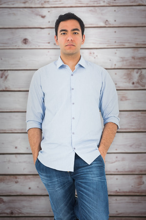 unsmiling: Unsmiling casual man standing against wooden planks