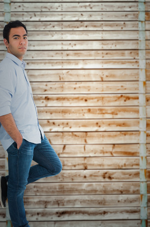 pale wood: Unsmiling casual man standing against wooden background in pale wood