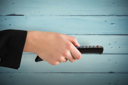 changing channel: Hand holding remote control against painted blue wooden planks