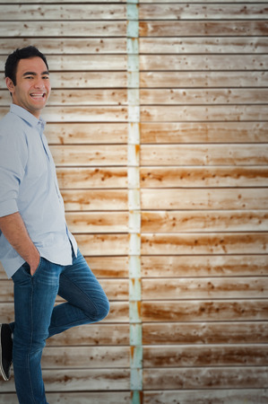 knees bent: Smiling casual man standing against wooden background in pale wood Stock Photo