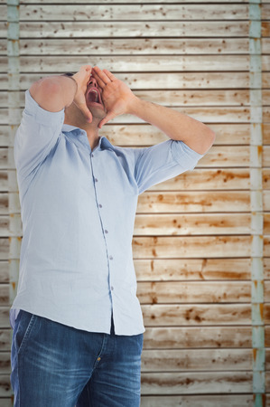 pale wood: Shouting casual man standing against wooden background in pale wood