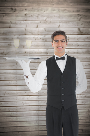 silver tray: Young waiter presenting a silver tray against wooden planks background Stock Photo