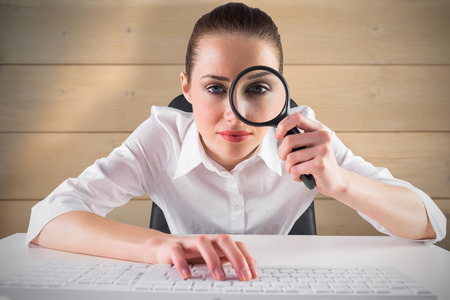 Businesswoman typing and looking through magnifying glass against bleached wooden planks background