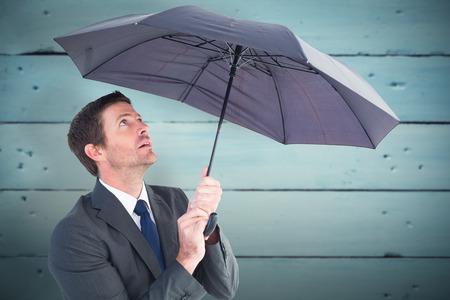 sheltering: Businessman sheltering under black umbrella against painted blue wooden planks