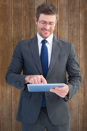 Businessman using his tablet pc  against wooden planks background photo