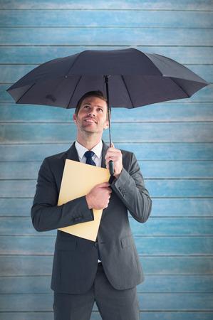sheltering: Businessman sheltering under umbrella holding file against wooden planks Stock Photo