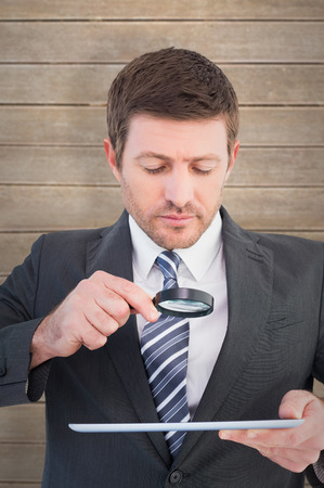 Businessman looking at tablet with magnifying glass against wooden planks photo