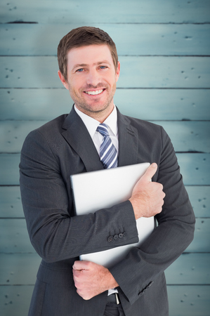 tightly: Businessman holding his laptop tightly against wooden planks