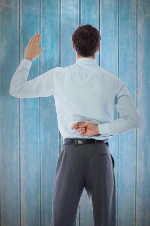 crossing fingers: Businessman crossing fingers behind his back against wooden planks