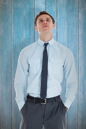 hands on pockets: Serious businessman standing with hands in pockets against wooden planks
