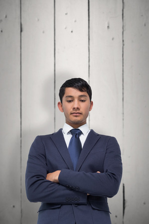 unsmiling: Unsmiling asian businessman with arms crossed against white wood Stock Photo