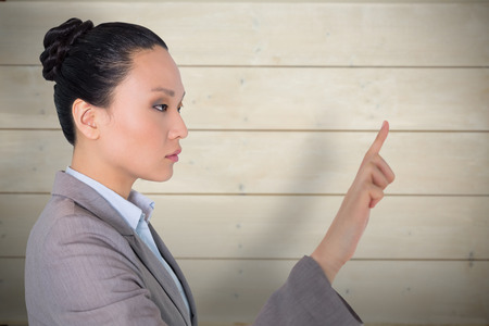 unsmiling: Unsmiling asian businesswoman pointing against bleached wooden planks background