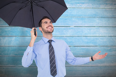 sheltering: Happy businessman sheltering with a black umbrella against wooden planks Stock Photo