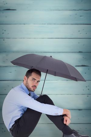 unsmiling: Unsmiling businessman holding umbrella sitting on the floor against wooden planks