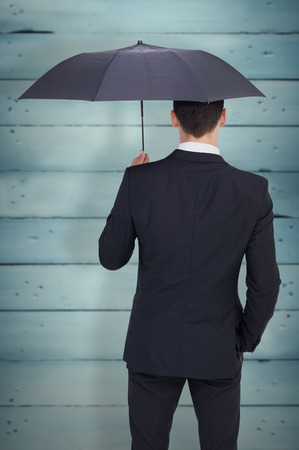 sheltering: Rear view of businessman sheltering with umbrella against wooden planks