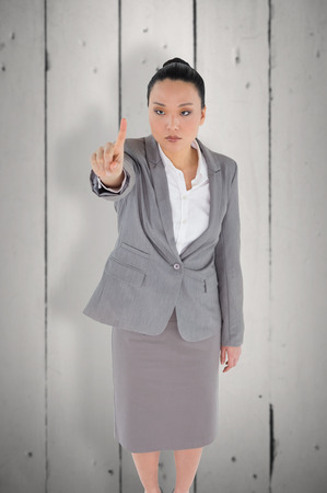 unsmiling: Unsmiling asian businesswoman pointing against white wood Stock Photo