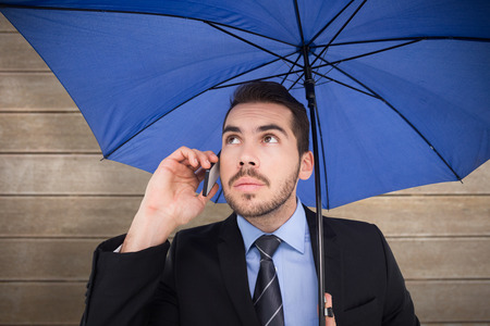 phoning: Serious businessman under umbrella phoning against wooden surface with planks