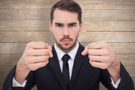 exasperated: Exasperated businessman with clenched fists  against wooden surface with planks Stock Photo