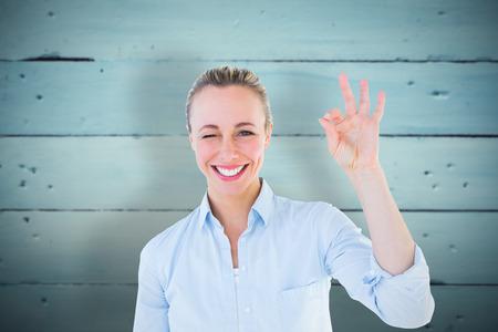 okay: Happy blonde making okay gesture against painted blue wooden planks