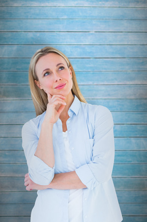 Smiling blonde thinking with hand on chin against wooden planks