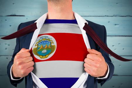 bandera de costa rica: Que abre la camisa del hombre de negocios para revelar la bandera de Costa Rica contra tablas de madera pintadas de azul