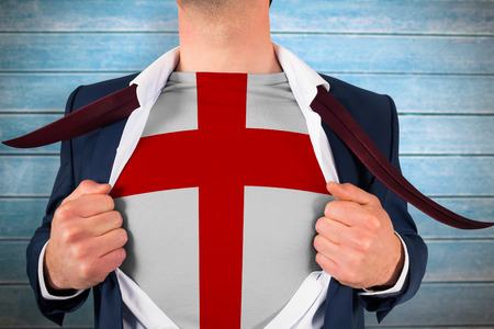 reveal: Businessman opening shirt to reveal england flag against wooden planks Stock Photo