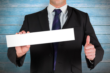 Businessman showing card against wooden planks photo