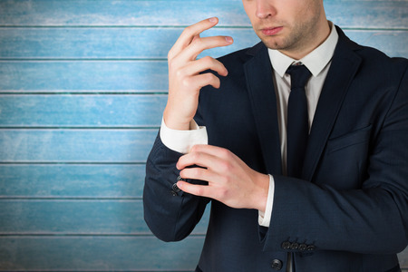 cuffs: Handsome businessman adjusting his cuffs against wooden planks Stock Photo
