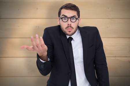 business skeptical: Doubtful businessman with glasses gesturing against bleached wooden planks background