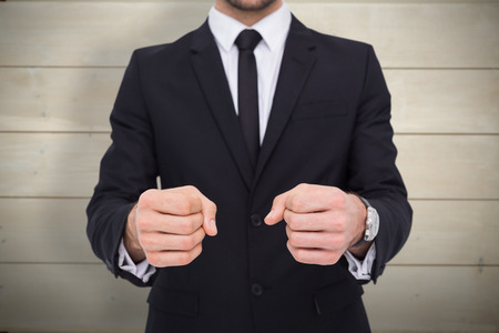 clenching fists: Elegant businessman in suit clenching his fists against bleached wooden planks background