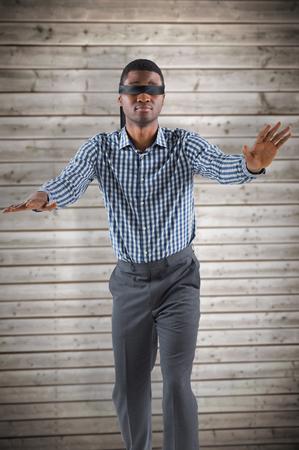 ojos vendados: hombre de negocios con los ojos vendados con los brazos hacia fuera contra el fondo tablones de madera