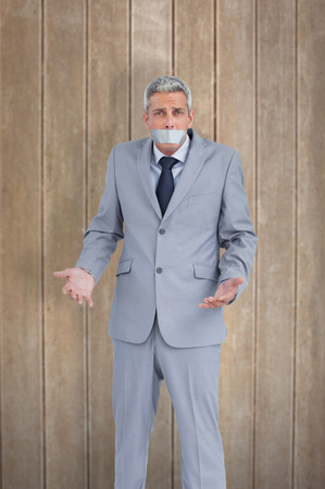 Businessman gagged with adhesive tape on mouth against wooden surface with planks