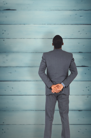 hands behind back: Young businessman standing with hands behind back against wooden planks