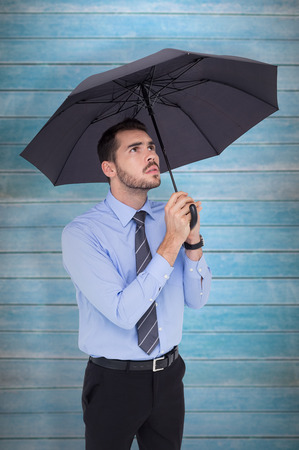 sheltering: Anxious businessman sheltering with umbrella  against wooden planks