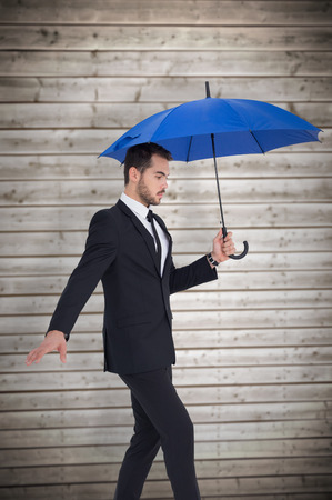 stepping: Concentrated businessman holding umbrella while stepping against wooden planks background