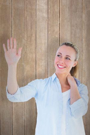 Blonde woman with hand raised against wooden surface with planks