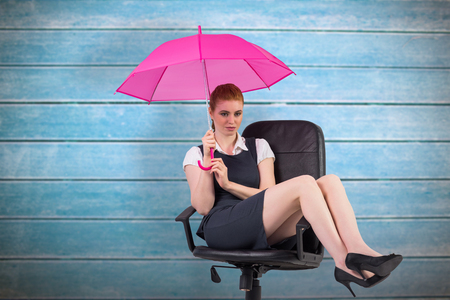 swivel: Businesswoman holding umbrella sitting on swivel chair against wooden planks