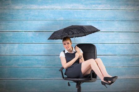 swivel chair: Businesswoman holding umbrella sitting on swivel chair against wooden planks